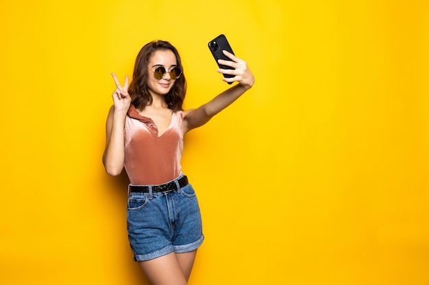 Pretty woman in dress making selfie isolated over yellow background