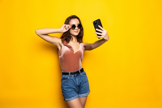 Pretty woman in dress making selfie isolated over yellow Free Photo