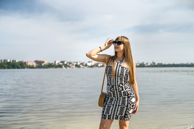 Pretty woman in dress near lake, summer time