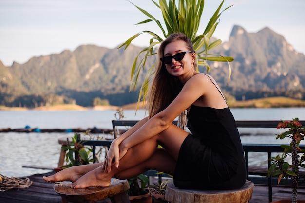 Bella donna in abito in vacanza, lago e montagne sullo sfondo