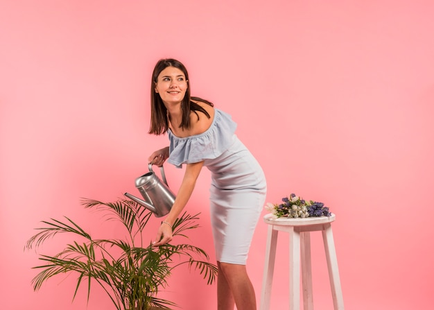 Pretty woman in dress watering green plant
