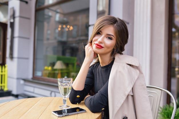Bella donna vestita in abito nero e trench beige con acconciatura alla moda e labbra rosse su una terrazza