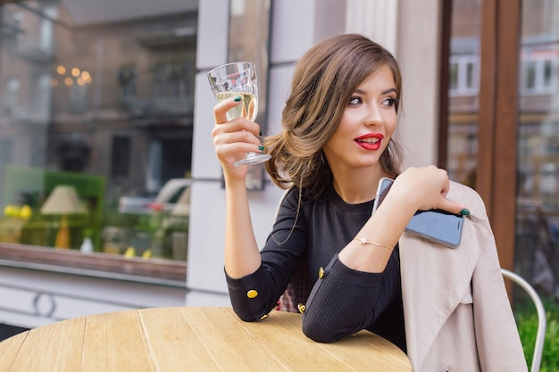 Pretty woman dressed in black dress and beige trench with stylish hairstyle and red lips on a terrace