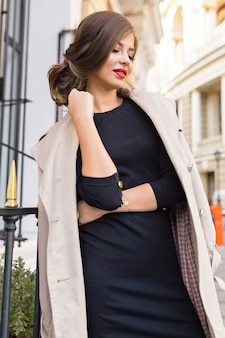 Красивая женщина, одетая в черное платье и бежевый тренч со стильной прической и красными губами на улице