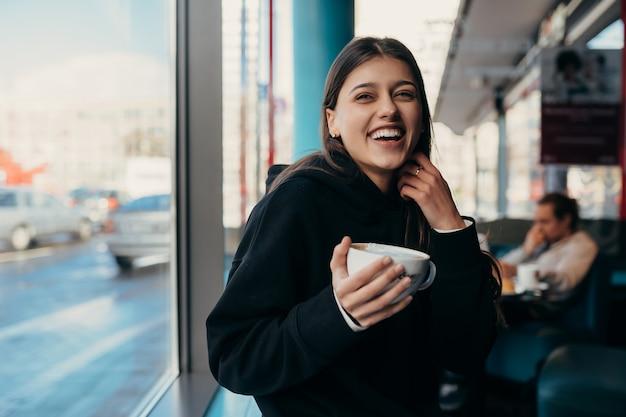Bella donna che beve caffè e sorridente
