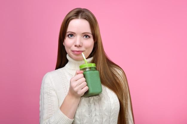 きれいな女性は緑のスムージーを飲む