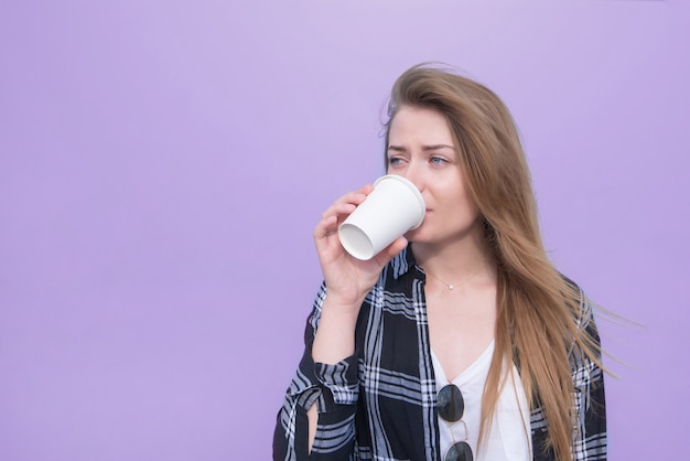 Pretty woman drinks a beverage from a white white glass on a purple background.