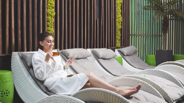 Pretty woman drinks tea at the spa and holds a smartphone in her hand