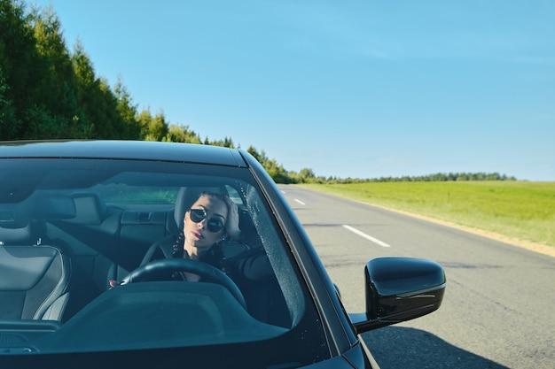Красивая женщина за рулем мощного автомобиля по проселочной дороге
