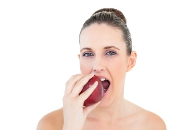 カメラを見ているリンゴを食べるかわいい女性