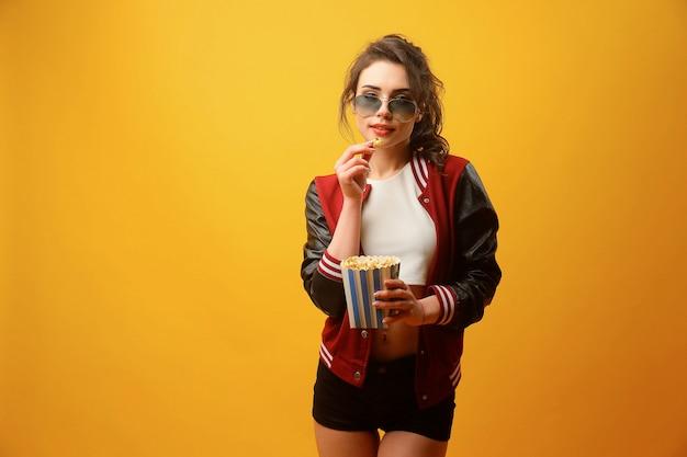 Красивая женщина ест попкорн в студии