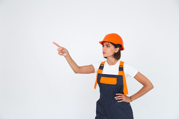 Pretty woman engineer in building protective helmet on white  angry swears at workers