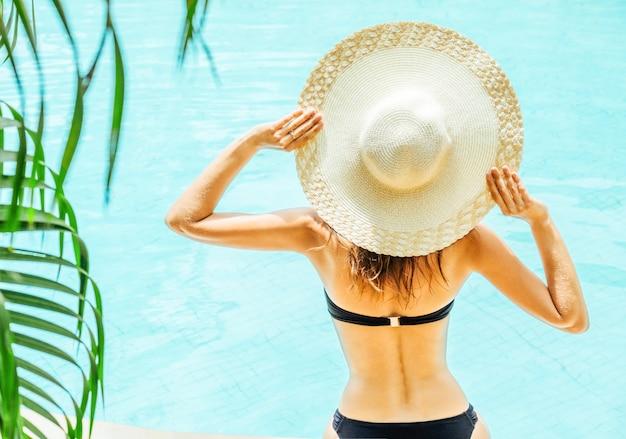 Красивая женщина, наслаждаясь бассейном на курорте