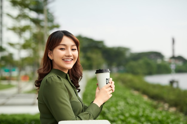 公園で温かい飲み物を楽しむきれいな女性