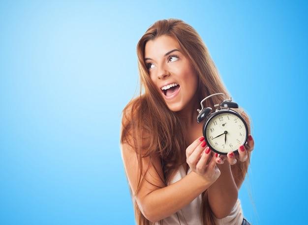 Pretty woman enjoying morning with alarm clock