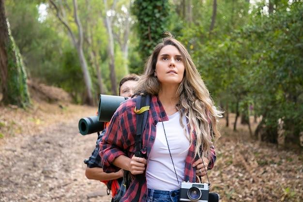 ビューとハイキングを楽しんでいるきれいな女性。一緒に森の中を歩くカップルの観光客。一緒にトレッキングするバックパックを持った若い白人ハイカーや旅行者。観光、冒険、夏休みのコンセプト