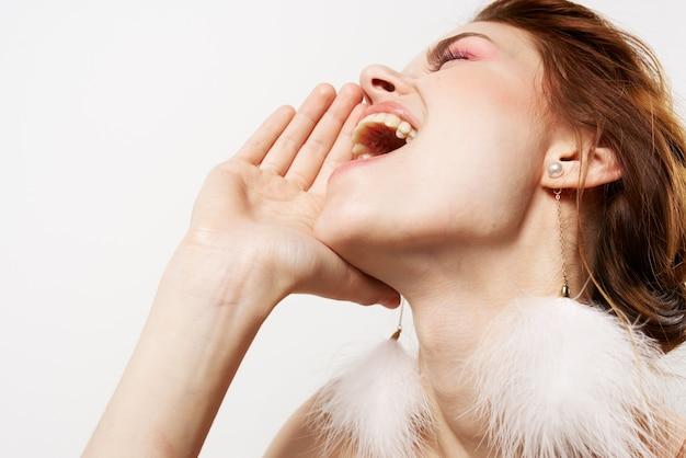 Красивая женщина закрытыми глазами пушистые серьги голые плечи гламур