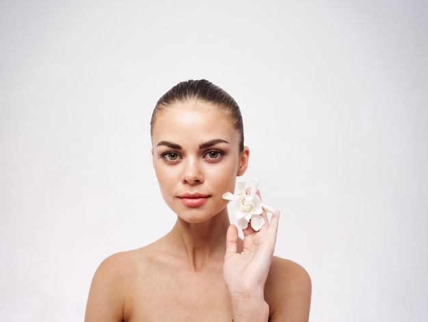 Pretty woman face makeup white flower naked shoulders light background
