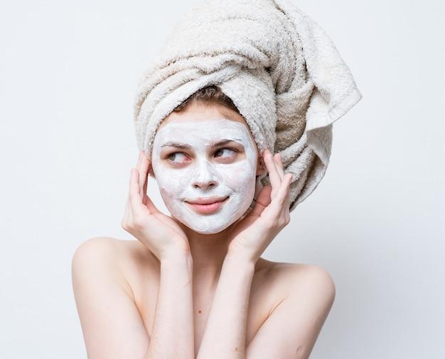 Красивая женщина лицо увлажняющий крем белая маска обнаженные плечи полотенца