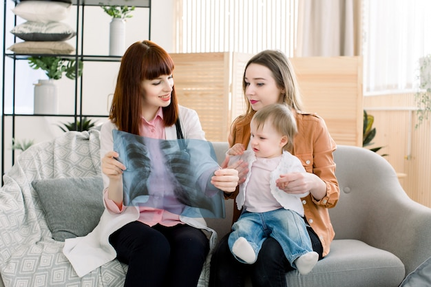 Pretty woman family doctor showing xray image to young mother with cheerful baby girl on her hands