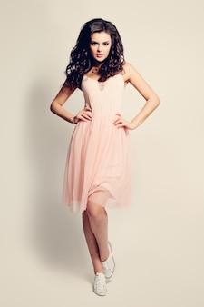 背景に立っているきれいな女性のファッションモデル。エレガントな女の子のポーズ。美容ファッションの肖像画