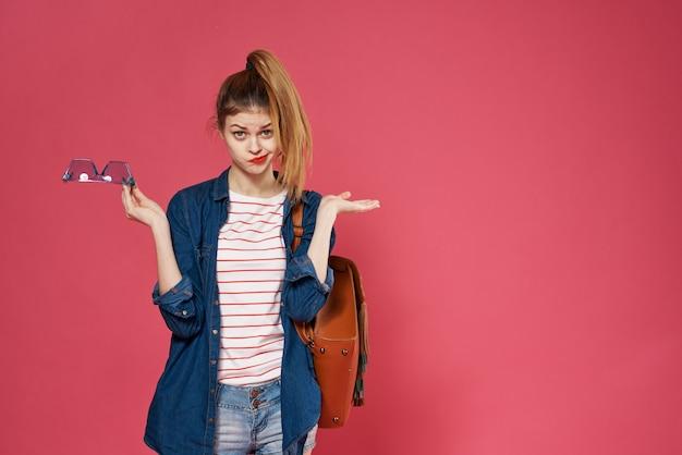 プリティウーマンファッショナブルな服スタジオバックパッククロップドビューピンクの背景