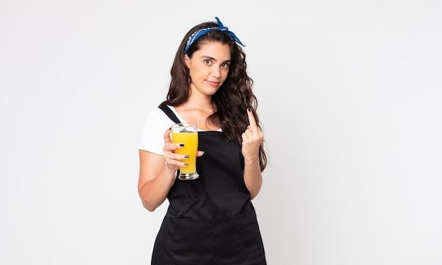 Красивая женщина злится, раздражается, бунтует и агрессивна и держит стакан апельсинового сока