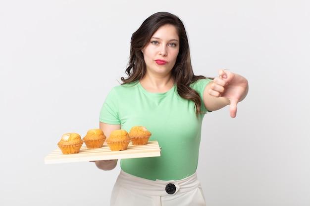 Красивая женщина чувствует себя крестно, показывает палец вниз и держит поднос с кексами