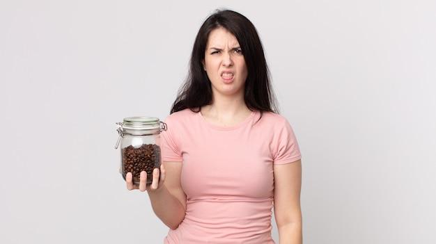 うんざりしてイライラし、舌を出してコーヒー豆のボトルを持っているきれいな女性