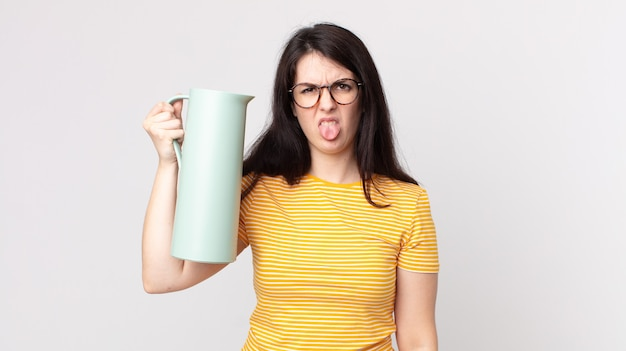 うんざりしてイライラし、舌を出してコーヒー魔法瓶を持っているきれいな女性