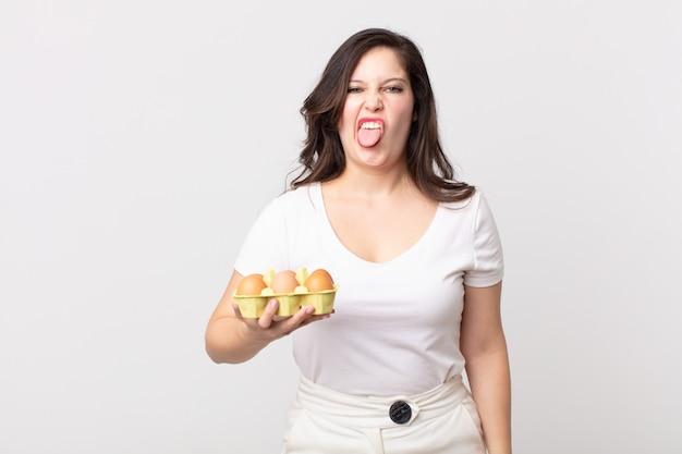 うんざりしてイライラし、舌を出して卵箱を持っているきれいな女性