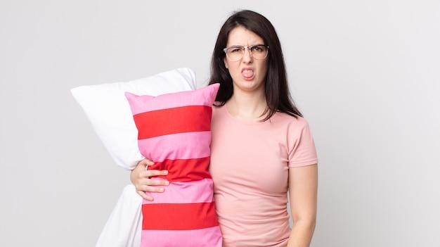 かなりの女性がうんざりしてイライラし、パジャマを着て枕を持って舌を出す