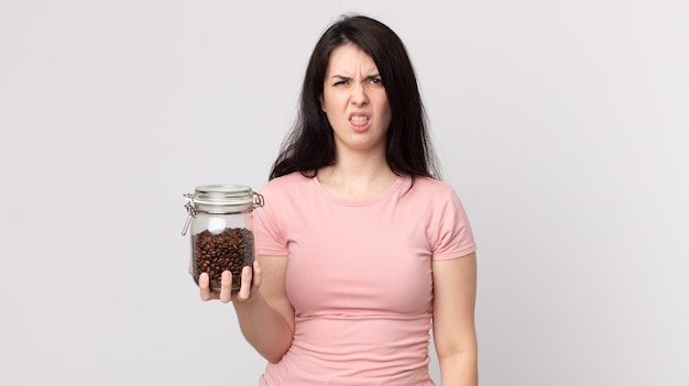 Pretty woman feeling disgusted and irritated and tongue out and holding a coffee beans bottle