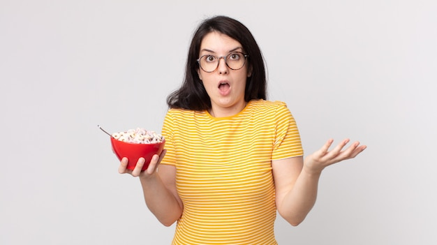 Pretty woman feeling extremely shocked and surprised and holding a breakfast bowl