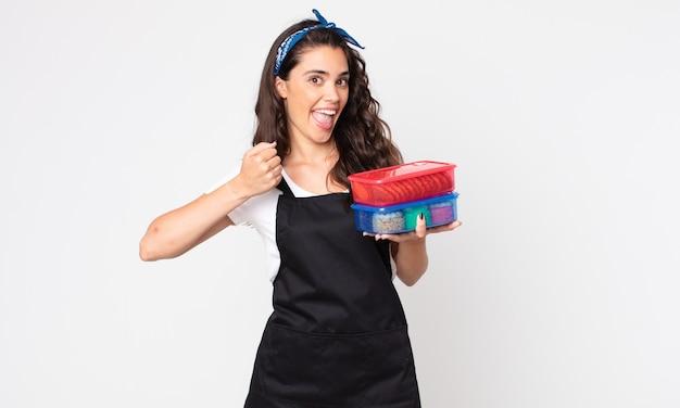 Красивая женщина чувствует себя счастливой и сталкивается с проблемой или празднует и держит посуду с едой