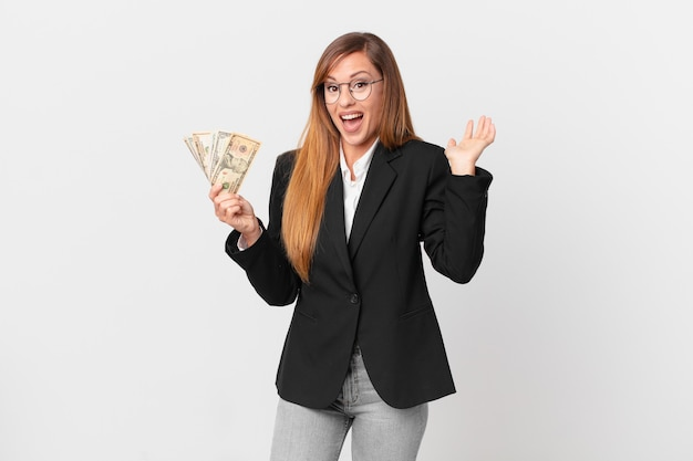 Pretty woman feeling happy and astonished at something unbelievable. business and dollars concept