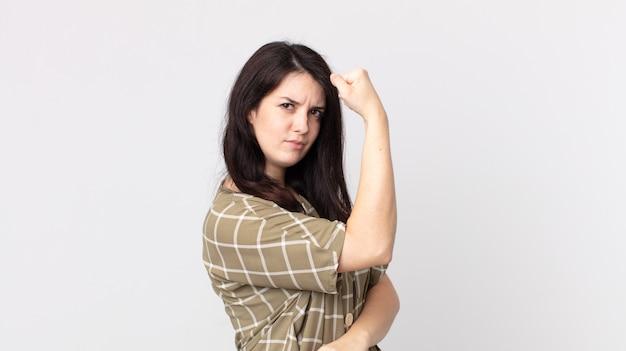 幸せ、満足、パワフル、屈曲フィット、筋肉の上腕二頭筋を感じ、ジムの後に強く見えるきれいな女性