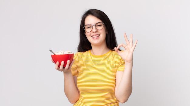 幸せを感じて、大丈夫なジェスチャーで承認を示し、朝食用のボウルを持っているきれいな女性