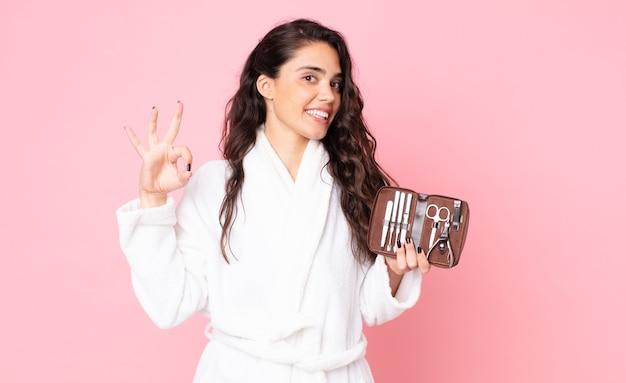 Красивая женщина чувствует себя счастливой, демонстрирует одобрение жестом и держит сумку для макияжа с инструментами для ногтей