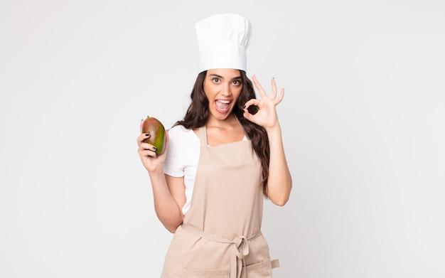 Красивая женщина чувствует себя счастливой, демонстрирует одобрение жестом в фартуке и держит манго