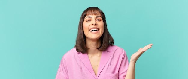 幸せ、驚き、陽気を感じ、前向きな姿勢で笑顔、解決策やアイデアを実現するきれいな女性