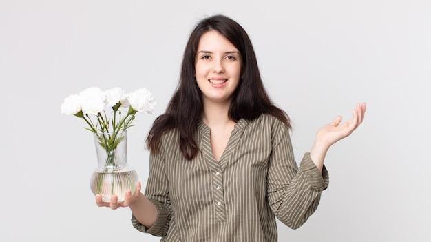 예쁜 여자는 행복하고, 해결책이나 아이디어를 깨닫고 장식용 꽃을 들고 놀랐습니다. 헤드셋이 있는 보조 에이전트