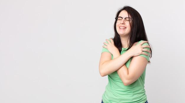 Симпатичная женщина чувствует себя влюбленной, улыбается, обнимает и обнимает себя, остается одинокой, эгоистичной и эгоцентричной