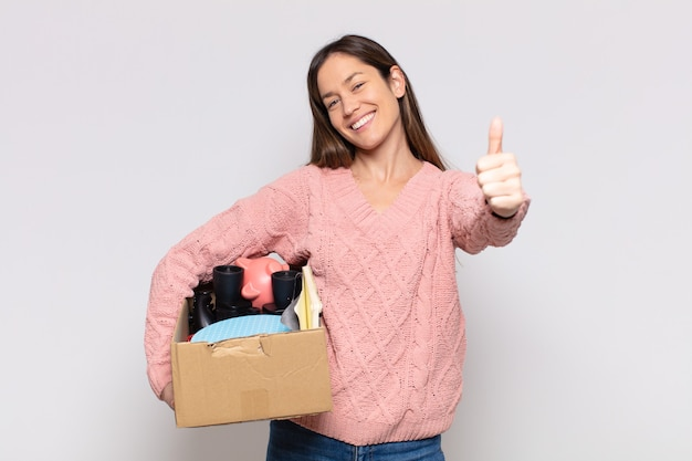 Красивая женщина чувствует себя гордой, беззаботной, уверенной и счастливой, позитивно улыбается и показывает палец вверх