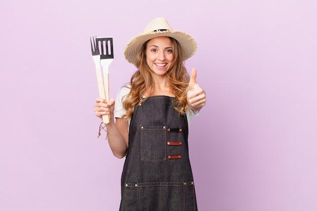 예쁜 여자가 자랑스러워하고 엄지손가락으로 긍정적으로 웃고 있습니다. 바베큐 요리사 개념
