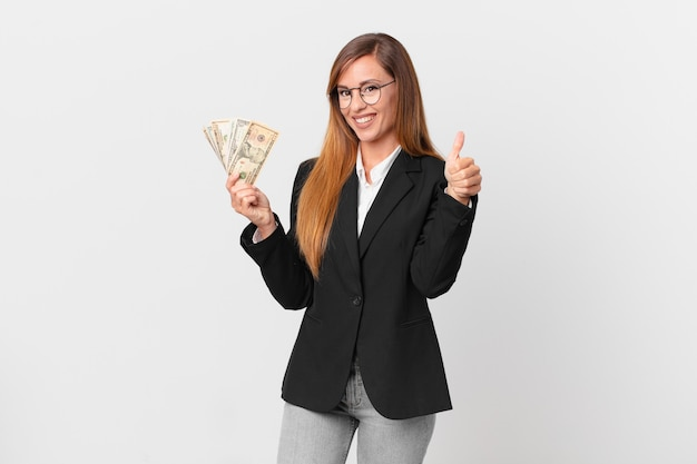 Pretty woman feeling proud,smiling positively with thumbs up. business and dollars concept