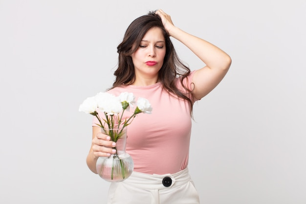 Красивая женщина чувствует себя озадаченной и сбитой с толку, почесывает голову и держит декоративный цветочный горшок