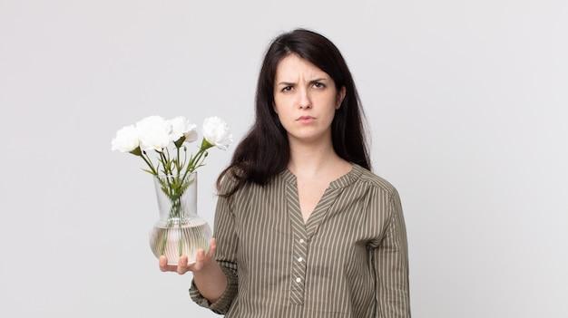 Красивая женщина чувствует себя грустно, расстроенной или сердитой, смотрит в сторону и держит декоративные цветы. помощник агента с гарнитурой