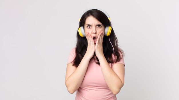 ヘッドフォンで音楽を聴いてショックと恐怖を感じているきれいな女性