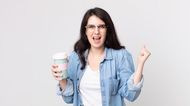 Красивая женщина в шоке, смеется, празднует успех и держит кофе на вынос